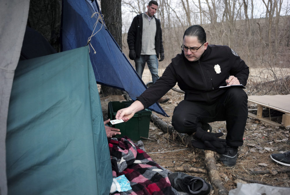 Worcester police officer Angel Rivera, right, returns a license to an unidentified man as Rivera asks if he has been tested for Hepatitis A at the entrance to a tent where the man spent the night in a wooded area, in Worcester, Mass. (Steven Senne/AP)