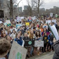 Students and supporters of the Massachusetts Youth Climate Strike  crowd around the steps of the State House. (Robin Lubbock/WBUR)