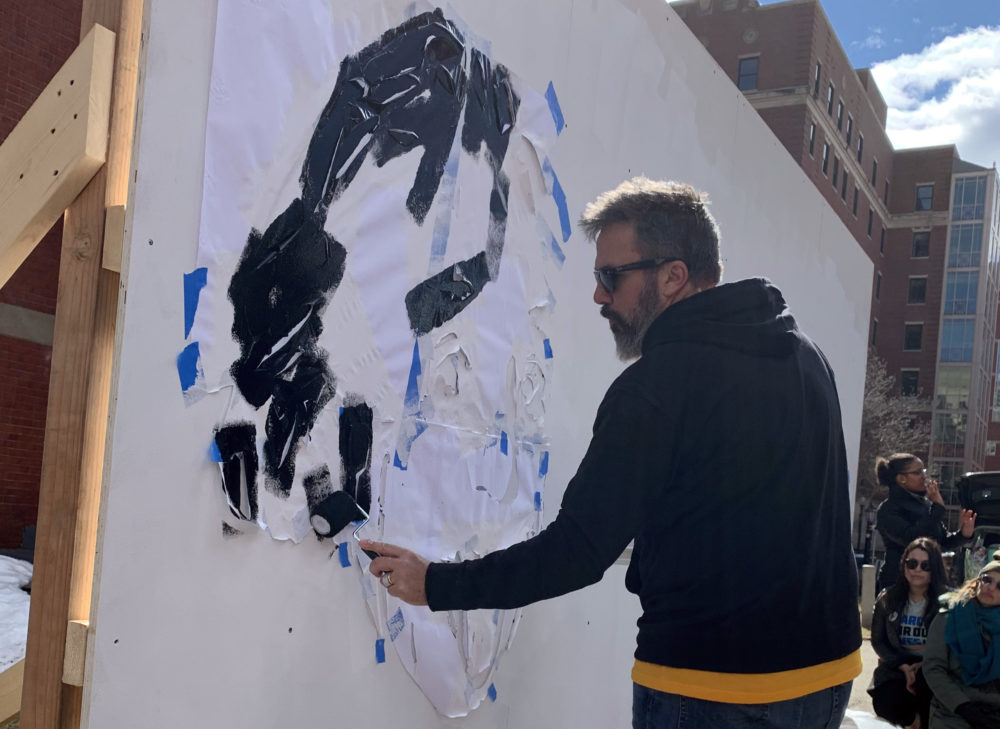 Manny Oliver starts a pop-up art installation with a stencil of Albert Einstein. (Simón Rios/WBUR)