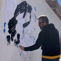 Manny Oliver starts a pop-up art installation with a stencil of Albert Einstein. (Simón Rios/WBUR)