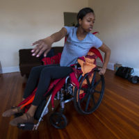 Ellice Patterson dances in her wheelchair at her home in Brookline. (Jesse Costa/WBUR)