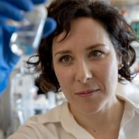 Catherine McCusker, assistant professor of biology, is seen at her lab at UMass Boston. (Robin Lubbock/WBUR)