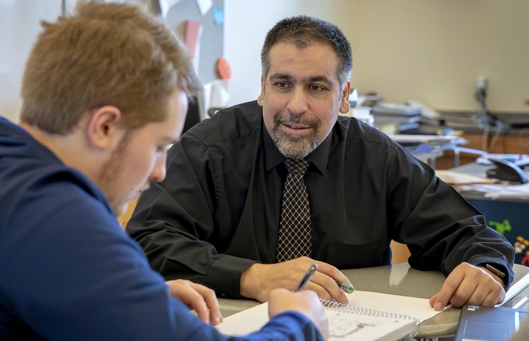 Jamil Siddiqui works on a calculus problem with senior Hunter Dempsey at East Bridgewater Junior/Senior High School. (Robin Lubbock/WBUR)