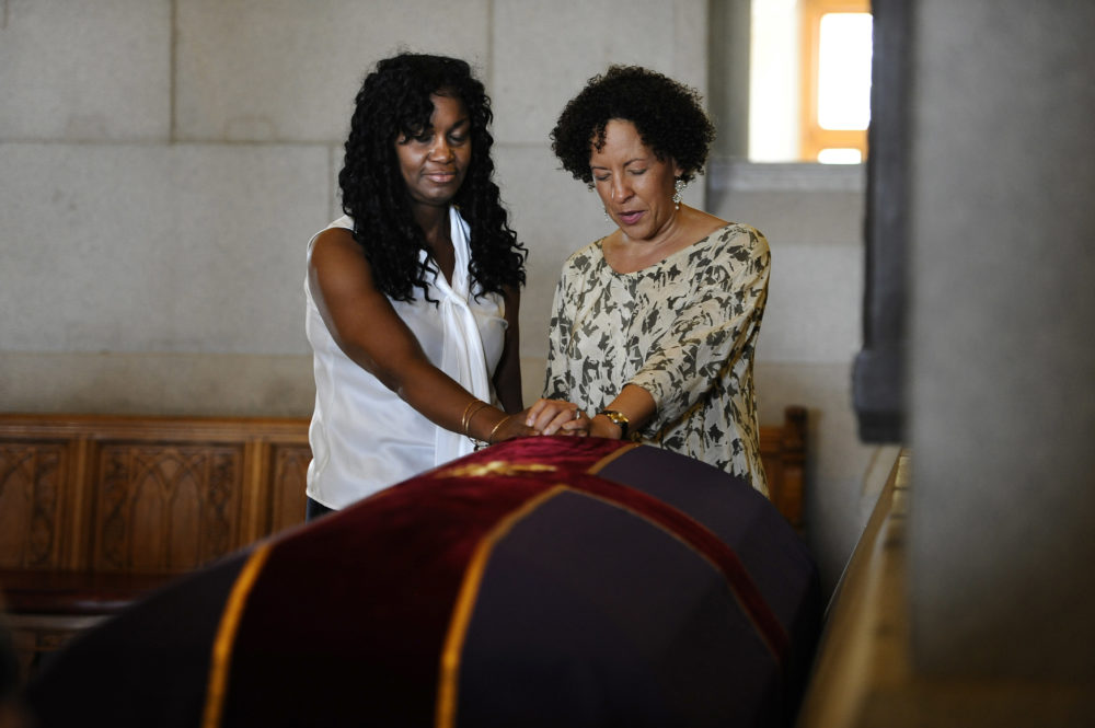 Tamara Lanier of Norwich, Conn., left, and Gabrielle Foreman of Delaware, pray over a casket with the remains of an enslaved man known as Mr. Fortune at the Capitol in Hartford, Conn., Sept. 12, 2013. (Jessica Hill/AP)