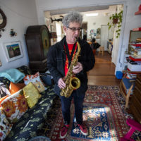 Musician and composer Ken Field playing saxophone at his apartment in Cambridge. (Jesse Costa/WBUR)