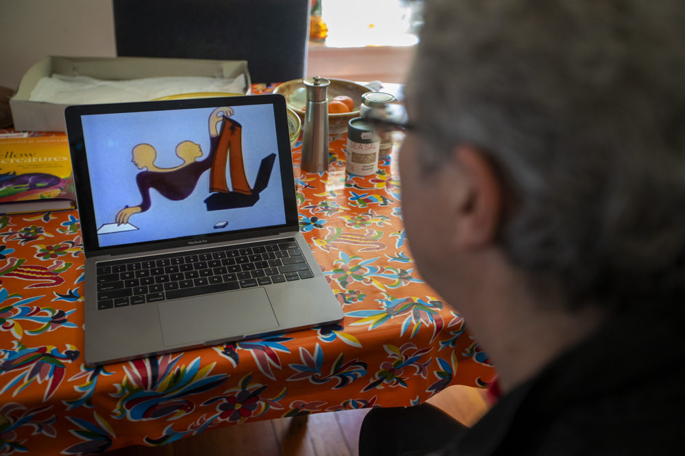 """Ken Field watches the animation created by his late wife, animator Karen Aqua, entitled """"Vis A Vis."""" (Jesse Costa/WBUR)"""
