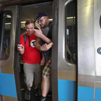 Dominic DiLuzio and Alex Cox rush out of a Blue Line train at Wonderland station after riding the entire MBTA subway and streetcar system. (Courtesy Dominic DiLuzio)