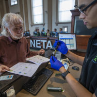 NETA associate Kyle Chambers examines a vaporizor cartridge and shows it to patient Richard Morse for his approval at the NETA marijuana dispensary in Brookline. (Jesse Costa/WBUR)
