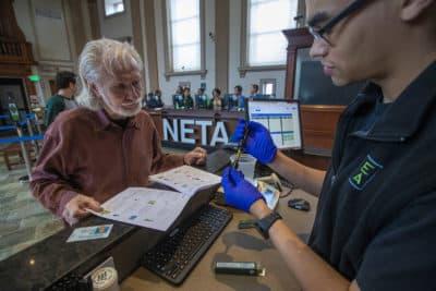 NETA associate Kyle Chambers examines a vaporizor cartridge and shows it to patient Richard Morse for his approval at the NETA marijuana dispensary in Brookline. (Jesse Costa/WBUR)