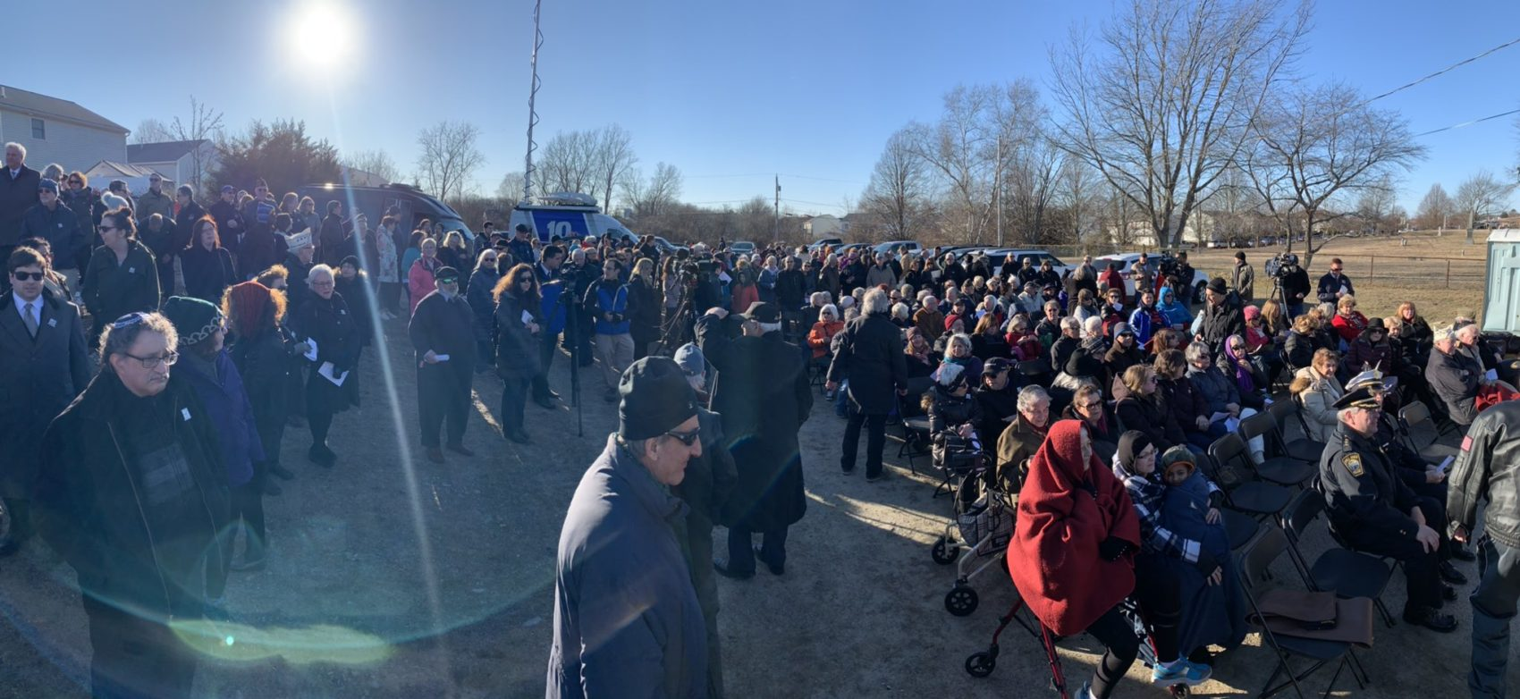 Hundreds gather at a Fall River Jewish cemetery for an antisemitism vigil after dozens of gravestones were vandalized. (Simón Rios/WBUR)