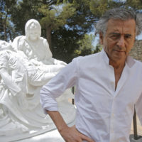 "French philosopher Bernard-Henri Lévy poses close to sculpture ""Merciful Dream"" by Jan Fabre during the preparations of the ""Adventures of truth"" exhibition in Saint Paul de Vence, France, on June 25, 2013. (Lionel Cironneau/AP)"