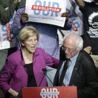 Sens. Elizabeth Warren, D-Mass., and Bernie Sanders, I-Vt., greet one another during a 2017 rally in Boston. Now they're both running for president. (Steven Senne/AP)