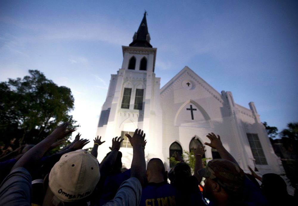 The men of Omega Psi Phi Fraternity Inc. lead a crowd of people in prayer outside the Emanuel AME Church in Charleston, S.C on June 6, 2015. (Stephen B. Morton/AP)