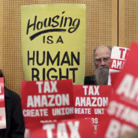 Members of the public look on at a Seattle City Council before the council voted to approve a tax on large businesses such as Amazon and Starbucks to fight homelessness in Seattle, May 14, 2018. (Elaine Thompson, File/AP)