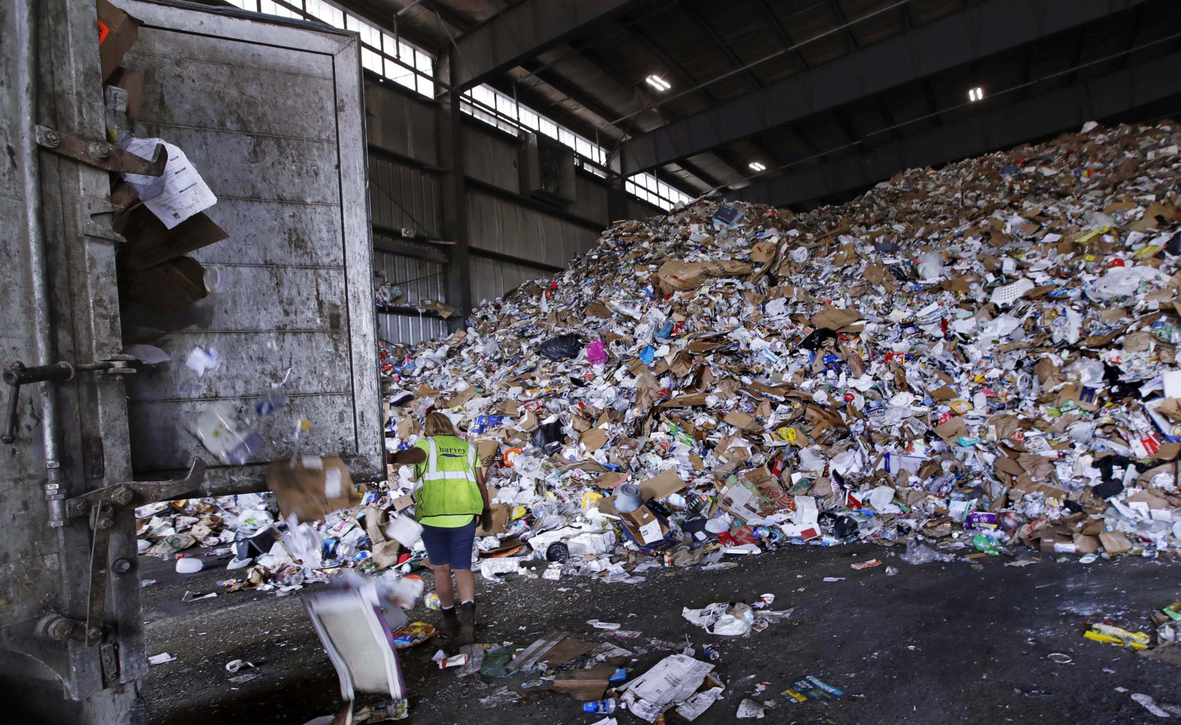 In this 2018 file photo, a trailer door is opened on a truck filled with unsorted recyclable refuse as it is offloaded and added to a giant pile in a processing building at EL Harvey & Sons, a waste and recycling company in Westborough. (Charles Krupa/AP)