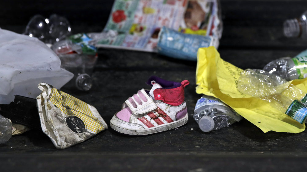In this 2018 file photo, a child's shoe is co-mingled with recyclable materials at EL Harvey & Sons, a waste and recycling company, in Westborough. (Charles Krupa/AP)