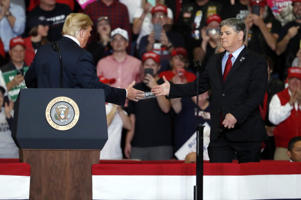 President Donald Trump shakes hands with Fox News Channel's Sean Hannity, right, during a campaign rally Monday, Nov. 5, 2018, in Cape Girardeau, Mo. (Jeff Roberson/AP)