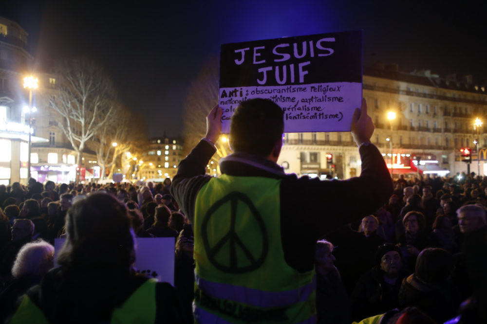 "A man wearing a yellow vest holds a placard reading ""I am jew"", during a gathering at the Republique square to protest against anti-Semitism, in Paris, France, Tuesday, Feb. 19, 2019. (Thibault Camus/AP)"