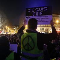 """A man wearing a yellow vest holds a placard reading """"I am jew"""", during a gathering at the Republique square to protest against anti-Semitism, in Paris, France, Tuesday, Feb. 19, 2019. (Thibault Camus/AP)"""
