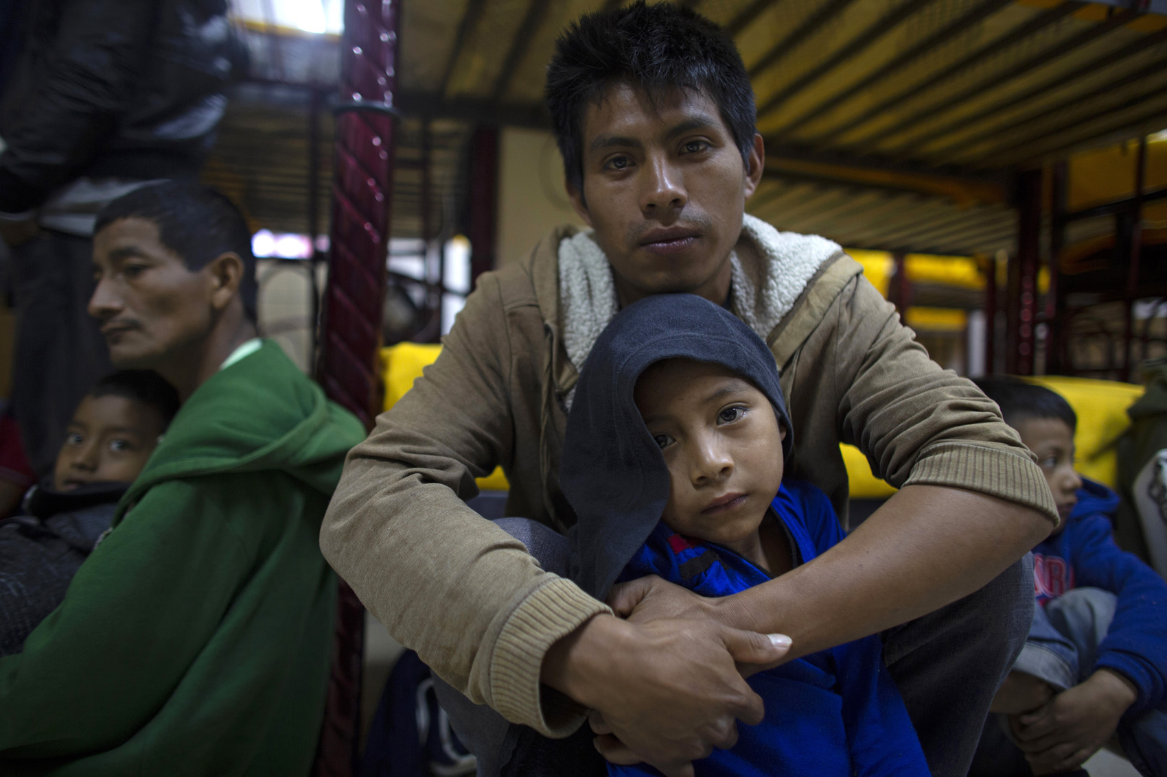 Abraham, 7, sits on the floor with his father, Miguel Martin, 27, at the San Juan Bosco migrant shelter, in Nogales, Mexico. Miguel left behind his wife and another son in hopes of getting enough work to buy some land in their hometown since they are now practically homeless in Guatemala. (Dario Lopez-Mills/AP)