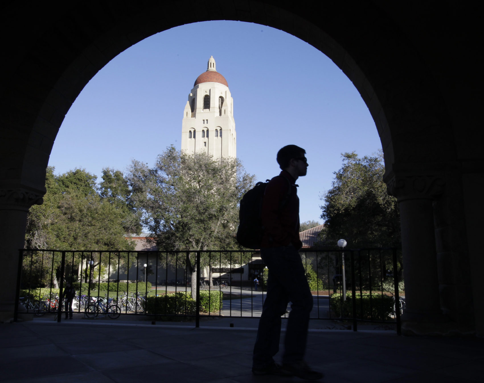 A Stanford University student walks in front of Hoover Tower on the Palo Alto, Calif. campus. Authorities have charged college coaches and others in a sweeping admissions bribery case. The charges were unsealed against coaches at Stanford, Wake Forest, Georgetown, the University of Southern California and the University of Southern California and University of California, Los Angeles.  (Paul Sakuma/AP)