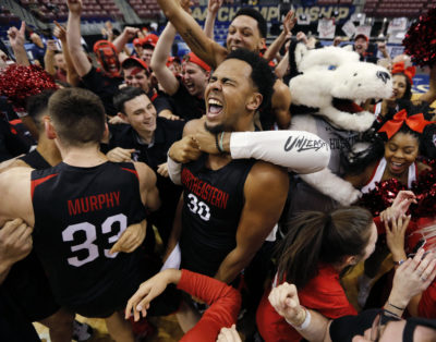 Northeastern's Anthony Green (30) celebrates with fellow players and fans after defeating Hofstra 82-74 in an NCAA college basketball game to win the Colonial Athletic Association men's basketball championship, Tuesday, March 12, 2019, in North Charleston, S.C. (AP Photo/Mic Smith)
