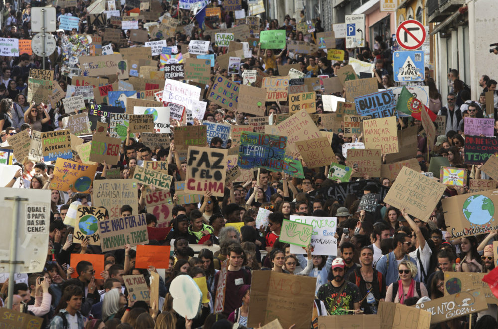 Thousands of high school students in Lisbon, Portugal, carry posters and chant slogans during a protest march through Lisbon while taking part in a global school strike for climate change (Armando Franca/AP)