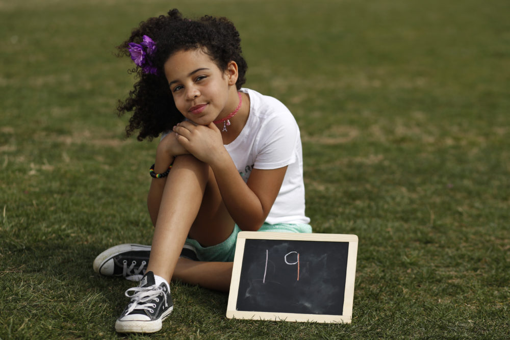 "On Friday, Havana Chapman-Edwards, 8, of Washington, sits by a chalkboard with her age in 2030, the point where the globe would be stuck on a path toward what scientists call planet-changing dangerous warming. ""Borders, languages and religions do not separate us,"" she said at the U.S. Capitol. (Jacquelyn Martin/AP)"