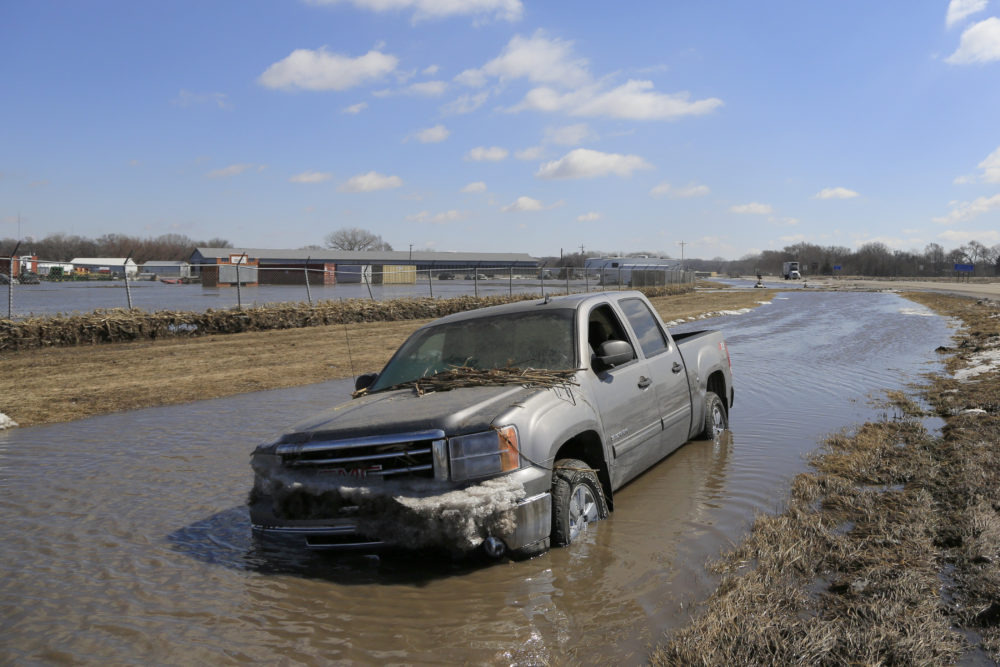 A pickup truck sits in a ditch after being swept by flood waters in Norfolk, Neb., Friday, March 15, 2019. Heavy rain falling atop deeply frozen ground has prompted evacuations along swollen rivers in Wisconsin, Nebraska and other Midwestern states. Thousands of people have been urged to evacuate along eastern Nebraska rivers as a massive late-winter storm has pushed streams and rivers out of their banks throughout the Midwest. (AP Photo/Nati Harnik)