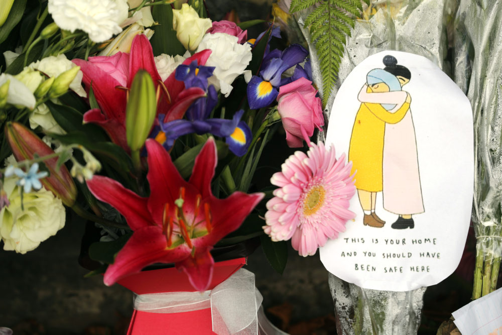 A message card is placed at a collection of flowers left at the Botanical Gardens in Christchurch, New Zealand, Saturday, March 16, 2019. (Vincent Thian/AP)