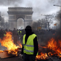 A protester stands in front of a barricade on fire during a yellow vests demonstration on March 16, 2019, in Paris. Paris police say more than 100 people have been arrested amid rioting in the French capital by yellow vest protesters and clashes with police. (Christophe Ena/AP)