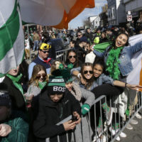 Spectators hold flags and cheer during the annual St. Patrick's Day parade, Sunday, March 17, 2019, in  South Boston. (Steven Senne/AP)