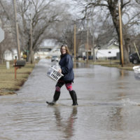 Akashi Haynes, left, and her daughter Tabitha Viers carry their belongings rescued from their flooded home in Fremont, Neb., Monday, March 18, 2019. (Nati Harnik/AP)