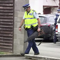 On March 19, 2019, a police officer carries a gun voluntarily surrendered by a member of the public into the Masterton police station in Masterton, New Zealand. (TVNZ via AP)