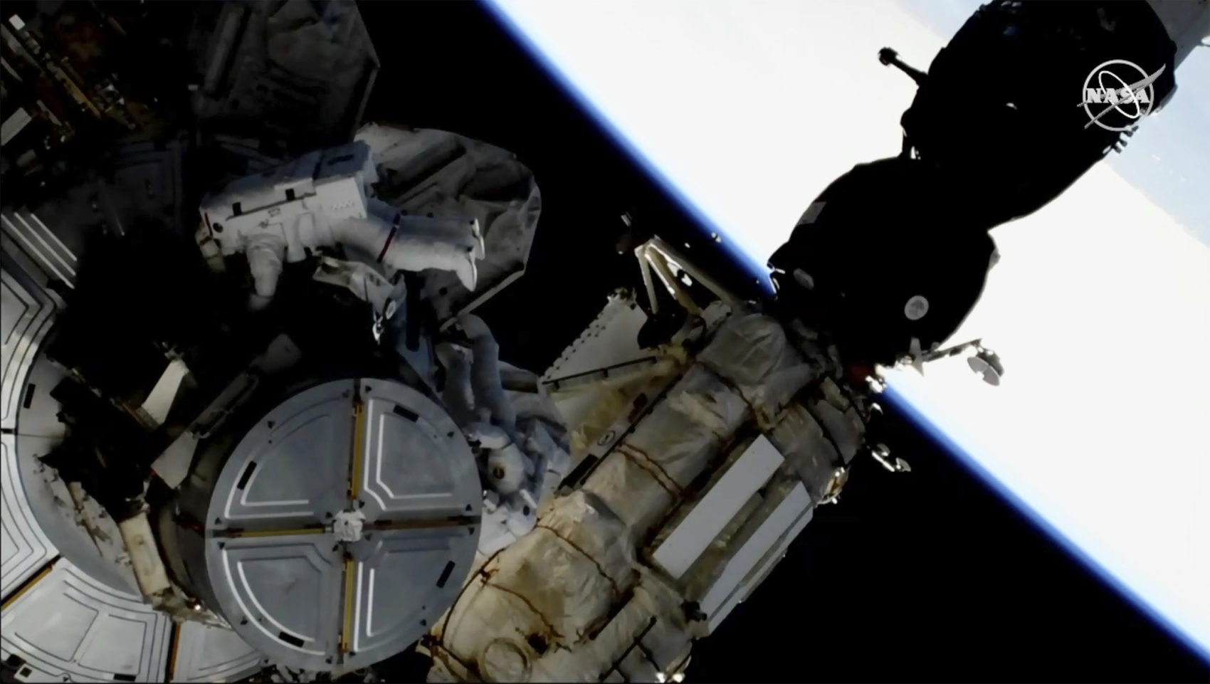 This image provided by NASA shows astronauts Anne McClain and Nick Hague taking a spacewalk to replace aging batteries on the International Space Station on Friday, March 22, 2019. (NASA via AP)