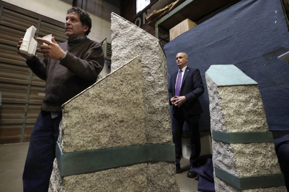 Artist Pablo Eduardo, left, speaks about granite pillars which will be part of a permanent memorial to the victims of the 2013 Boston Marathon bombings. Listening at right is Boston's Chief of Operations Patrick Brophy. (Elise Amendola/AP)