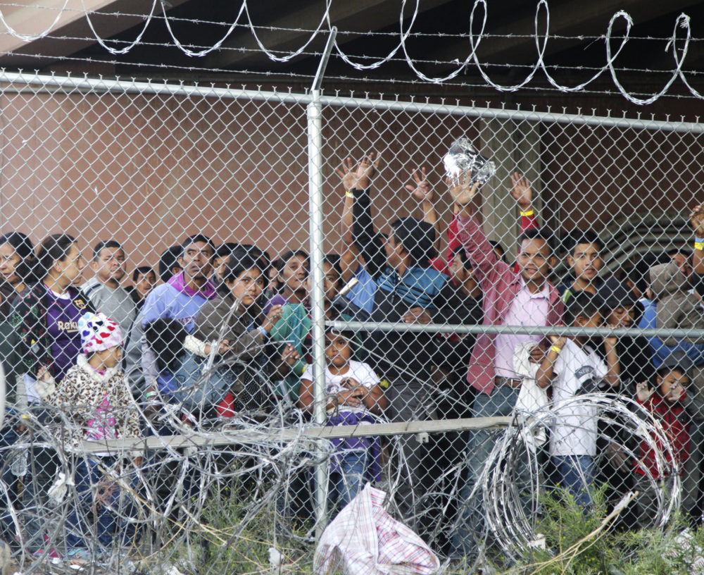 Migrants wait for food in El Paso, Texas, on Wednesday, March 27, 2019, in a pen erected by U.S. Customs and Border Protection to process a surge of migrant families and unaccompanied minors. Earlier on Wednesday, Customs and Border Protection Commissioner Kevin McAleenan announced the the Trump administration will temporarily reassign several hundred border inspectors. (Cedar Attanasio/AP)