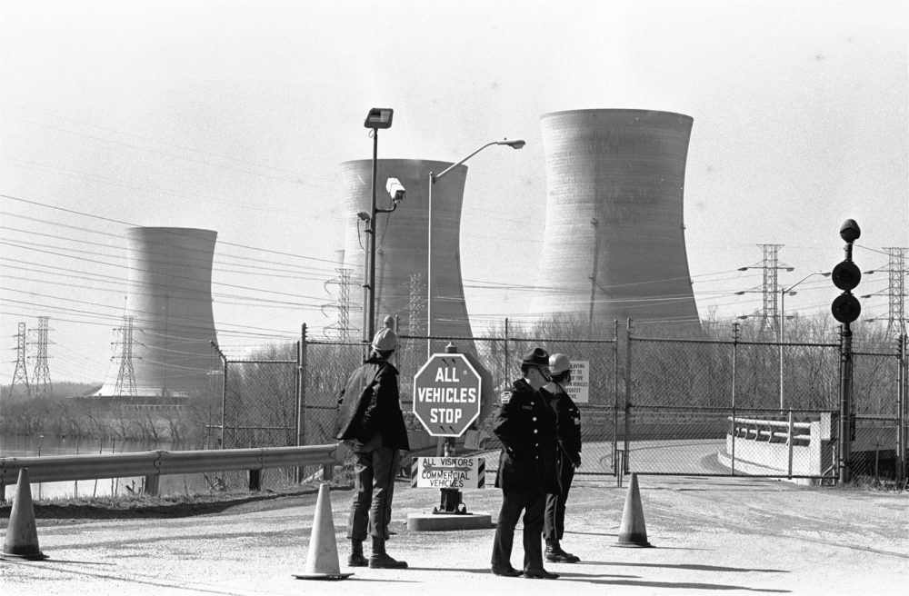 In this undated photo, a Pennsylvania state police officer and plant security guards stand outside the closed front gate to the Metropolitan Edison nuclear power plant on Three Mile Island near Harrisburg, Pa., after the plant was shut down following a partial meltdown on March 28, 1979. (Paul Vathis/AP/File)