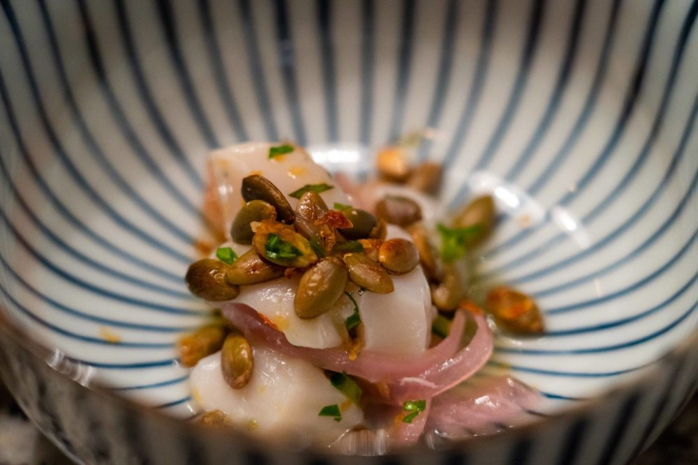 This scallop crudo dish, created by Dope Dinners, features lacto-fermented red onion, lime juice, toasted pepitas, CBD tomato salt. (Courtesy)