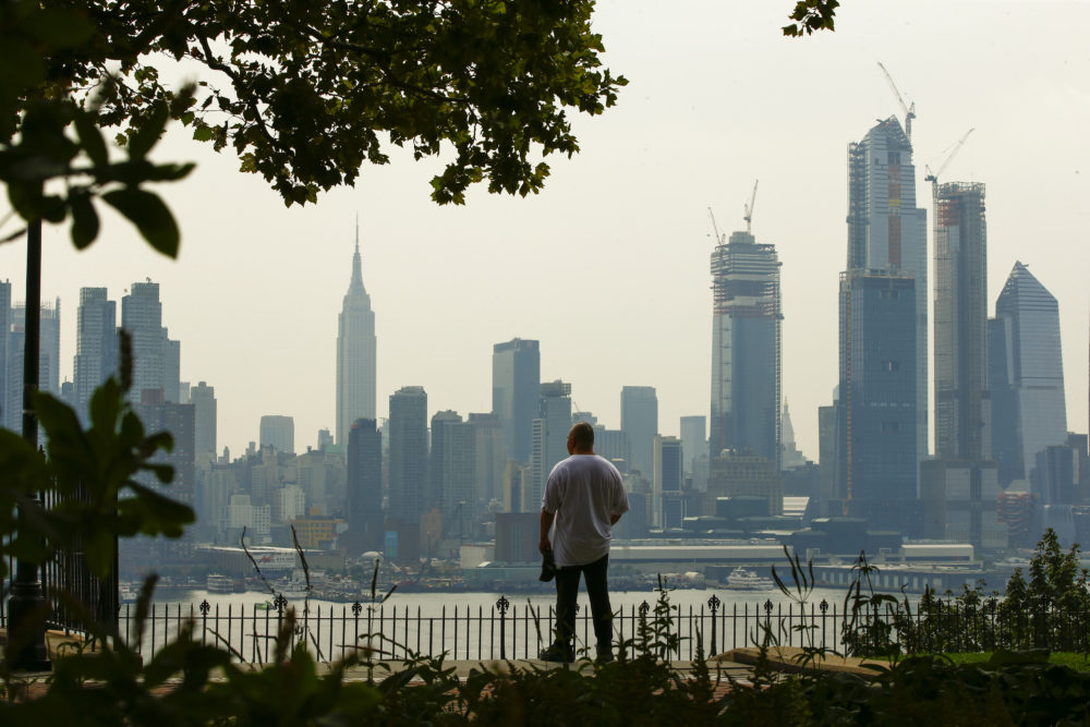 A man takes a look at the haze over the New York skyline during a heat advisory on August 17, 2018, in Weehawken, New Jersey. (Eduardo Munoz Alvarez/Getty Images)