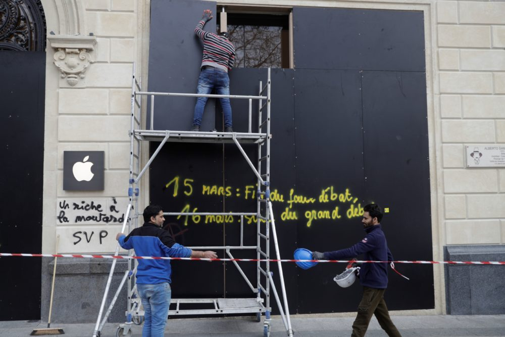 Men work to install wooden boards on the damaged window of an Apple store on the Champs-Elysees avenue in Paris on March 17, 2019, a day after the 18th consecutive Saturday of demonstrations called by the yellow vest movement. (Geoffroy Van Der Hasselt/AFP/ Getty Images)