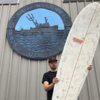 Korey Nolan with his surfboard made from old Dunkin' cups. (Courtesy photo)