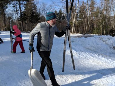 Windblown ski area owner Al Jenks spent a sunny Friday in late February skiing around his property, using a shovel to cover up persistent bare patches of ground with fresh snow. (Annie Ropeik/NHPR)