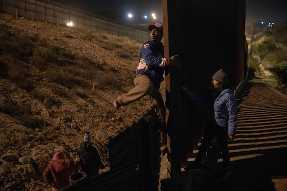 Migrants scope out and try to find a place to cross the U.S. - Mexican border wall near the beach in Tijuana, Mexico, on December 16, 2018. Some attempt to dig under the wall, while others pass over it. (Kitra Cahana/MAPS)