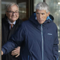 """William """"Rick"""" Singer, front, founder of the Edge College & Career Network, exits federal court in Boston on Tuesday, March 12, 2019, after he pleaded guilty to charges in a nationwide college admissions bribery scandal. (Steven Senne/AP)"""