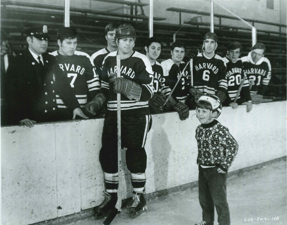 """Ryan O'Neal dons his Harvard hockey uniform for the movie """"Love Story."""" Bill Cleary III is in foreground. (Courtesy Bill Cleary)"""