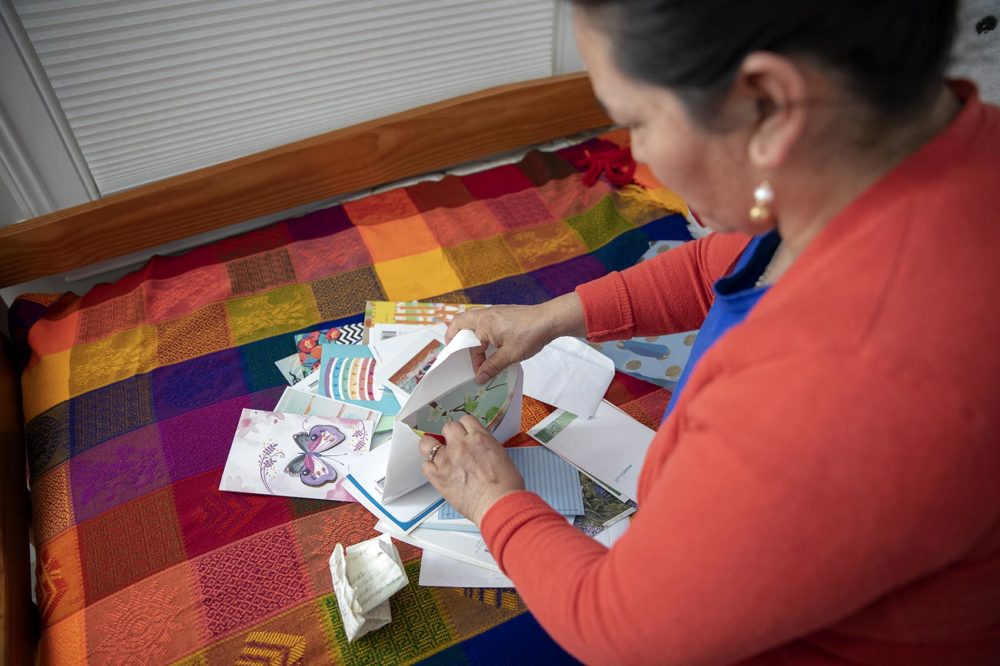 """Maria Merida sifts through birthday cards she received last year from members of the church congregation where she's been living in """"sanctuary"""" for more than a year. (Robin Lubbock/WBUR)"""