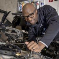 Rich Benoit reaches inside a damaged Tesla he's working on in his garage. (Robin Lubbock/WBUR)