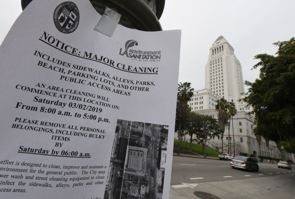 A notice alerting the public and homeless who stay nearby that the area around the Los Angeles City Hall will undergo a major cleaning to combat a rat infestation inside the building is posted nearby in Los Angeles on March 1, 2019. (Mark Ralston/AFP/Getty Images)