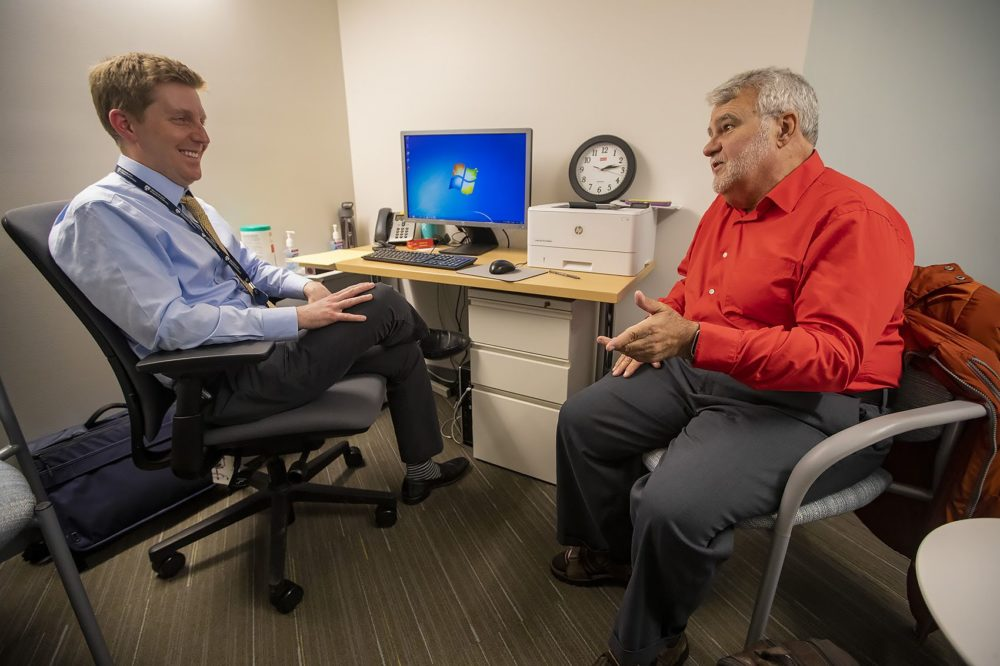 A patient speaks with Dr. David Kroll about some of the issues he is experiencing during his visit at the urgent care facility at the Brigham and Women's Psychiatric Specialties Clinic. (Jesse Costa/WBUR)